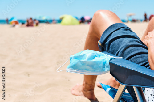 Stampa su Tela mask and man sitting in a deck chair on the beach