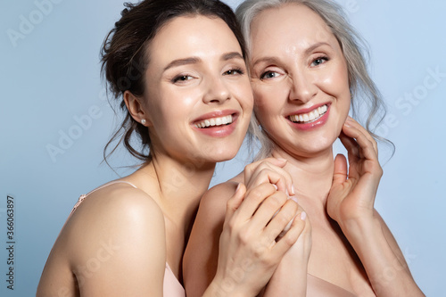 Cuadros en Lienzo Happy smiling   grey-haired senior mother and  young daughter holding hand and h