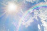 Fototapeta Tęcza - Summer sun burst and blue sky  rainbow - massive sun radiating beside fluffy clouds with a giant arcing rainbow and beautiful blue summer sky with copy space for messages