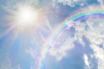 Summer sun burst and blue sky  rainbow - massive sun radiating beside fluffy clouds with a giant arcing rainbow and beautiful blue summer sky with copy space for messages