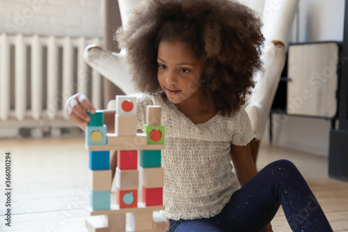 Playful little african American girl sit on warm floor at home play construct tower with wooden bricks, cute small biracial child have fun enjoy game with blocks or cubes, education, learning concept