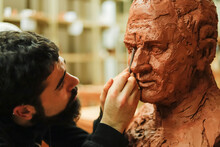 Focused Sculptor Finishing A C...
