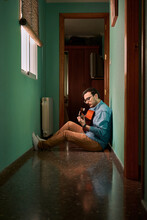 Young Man Plays Guitar Sitting In The Hallway Of His House
