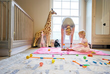 Young Mother Stretching While Toddler Daughter Plays In Nursery