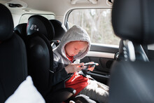 Boy Sat In His Car Seat Playing A Nintendo Video Game Console