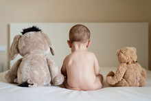 Rear View Of A Naked Baby Sitting Up In Bed With Two Teddy Bears