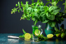 Mint Tea With Lime Slices And Bunch Of Fresh Mint On A Dark Background.