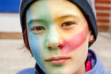 Portrait Of Beautiful Boy With Colorful Face Paint And Direct Gaze