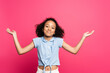canvas print picture - smiling cute curly african american kid showing shrug gesture isolated on pink