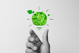 Fototapeta Kawa jest smaczna - Corporate Social Responsibility(CSR), eco-friendly business concepts with businessman hand holding crumpled green paper light bulb