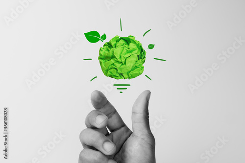 Obraz Corporate Social Responsibility (CSR), eco-friendly business concepts with businessman hand holding crumpled green paper light bulb - fototapety do salonu