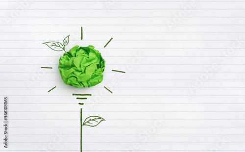Fototapeta Green crumpled paper light bulb on white notebook paper background, Corporate Social Responsibility(CSR) concept obraz