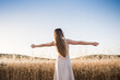 Young woman on her back opens her arms in the field feeling free. Blonde girl with long hair enjoys the summer sun