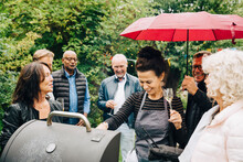 Smiling Female Friends Cooking Dinner On Barbecue Grill During Party While It Rains