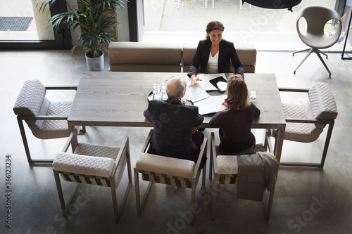 Canvas Print High angle view of female lawyer and customers sitting at desk in office