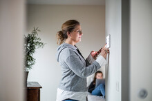 Mother Holding Smart Phone While Using Digital Tablet On Wall With Daughter In Background At Smart Home