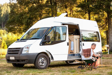 Man Sitting In Front Of Campervan On Campground In New Zealand