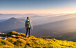 Leinwandbild Motiv Beautiful mountains in fog and standing young woman with backpack on the peak at sunset in summer. Landscape with sporty girl, green grass, forest, hills , blue sky with sunbeams. Travel and tourism
