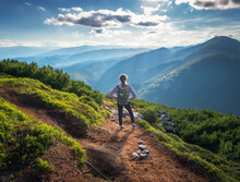 Beautiful Mountains And Standing Young Woman With Backpack On The Trail At Sunset In Summer. Landscape With Sporty Girl On The Mountain Peak, Forest, Hills , Blue Sky With Clouds And Sunbeams. Travel
