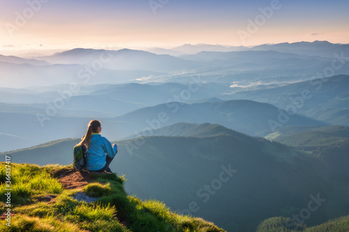 Fototapeta Young woman with backpack sitting on the mountain peak and beautiful mountains in fog at sunset in summer. Landscape with sporty girl, green grass, forest, hills , sky, sunbeams. Travel and tourism obraz