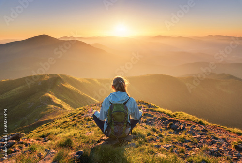 Obraz Young woman with backpack sitting on the mountain peak and beautiful mountains in fog at sunset in summer. Landscape with sporty girl, green forest, hills , sky, sunbeams. Travel and tourism. Yoga - fototapety do salonu