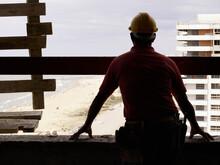 Hispanic Worker Looking Down F...