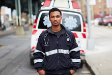 Portrait Of Young Man Standing In Front Of Ambulance On Street