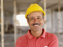 Hispanic Worker Smiling On Con...