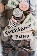 Close-up Of Coins And Banknotes In Jar Labeled Emergency Found
