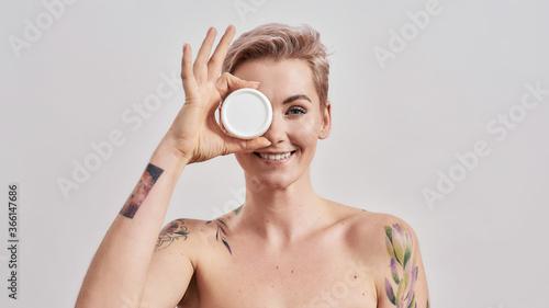 Fotografija Portrait of beautiful tattooed woman with pierced nose and short hair hiding eye