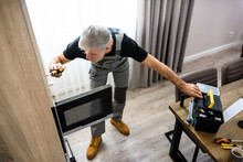 Full Length Shot Of Aged Repairman In Uniform Working, Fixing Broken Microwave In The Kitchen Using Screwdriver. Repair Service Concept