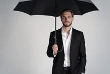 Businessman In A Suit Standing Under Black Umbrella