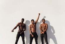 Three Men Raising Fists In Pro...