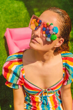 Portrait Of Woman Wearing Glasses With Colourful Pom Poms