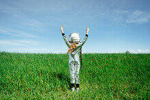 Rear View Of Girl In Astronaut Costume Standing With Peace Sign On Grass