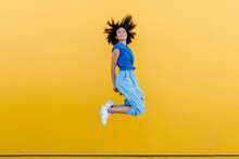 Pretty Woman Jumping For Joy In Front Of Yellow Wall