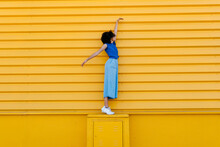 Happy Young Woman Balancing On Platform In Front Of Yellow Wall