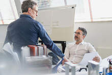 Mature Businessmen Discussing Over Document While Sitting In Office