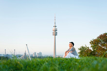 Thoughtful Young Woman Sitting On Grassy Land With Olympic Tower In Background At Munich, Germany