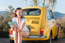 Portrait Of Laughing Woman With Map Sitting On Bumper Of Yellow Vinage Car, Sardinia, Italy