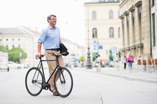 Smiling Businessman Looking Away While Walking With Bicycle On Road In City