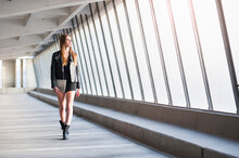 Fashionable Young Woman Holding Laptop While Walking In Building