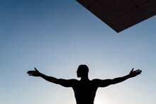 Silhouette Of Man Stretching Out Arms, Against Clear Sky