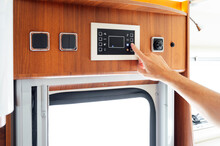 Hand Of Man Pressing Button On Motor Home Control Panel