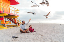 Father Sitting With Daughter Feeding Seagulls At Miami Beach Against Sky, Florida, USA