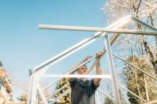 Man Building Greenhouse In Yar...