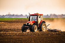 Farmer In Tractor Plowing Farm Against Sky