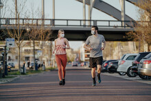 Young Couple Jogging On Road I...