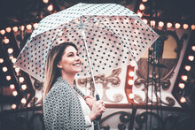 Cheerful Woman Looking At Something And Holding A Dotted Umbrella At A Carnival
