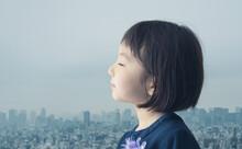 目を閉じる少女と都市